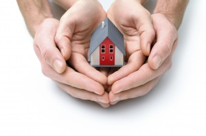 Human hands holding small model of house