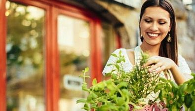 A lady looking at herbs in front of her business
