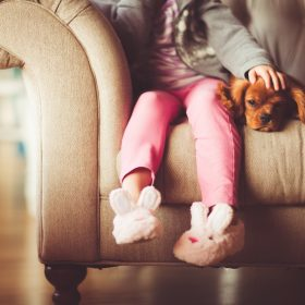 girl sitting on couch with dog
