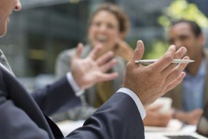 Businessman gesturing in meeting with colleagues