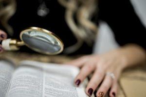 A selective closeup shot of a person reading a book through a magnifying glass